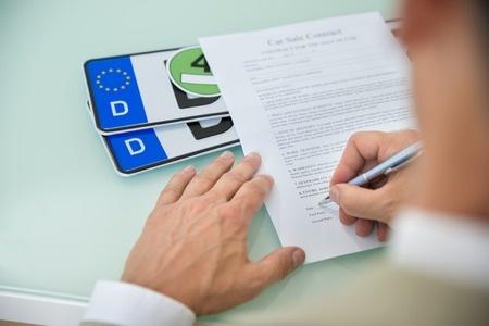 Fotografia firmando unos papeles para importacion de un vehiculos desde Suiza