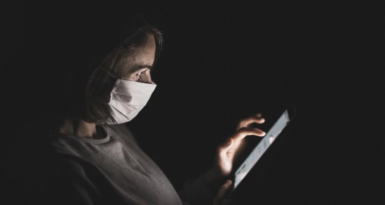 Mujer con mascarilla consultando tableta electrónica